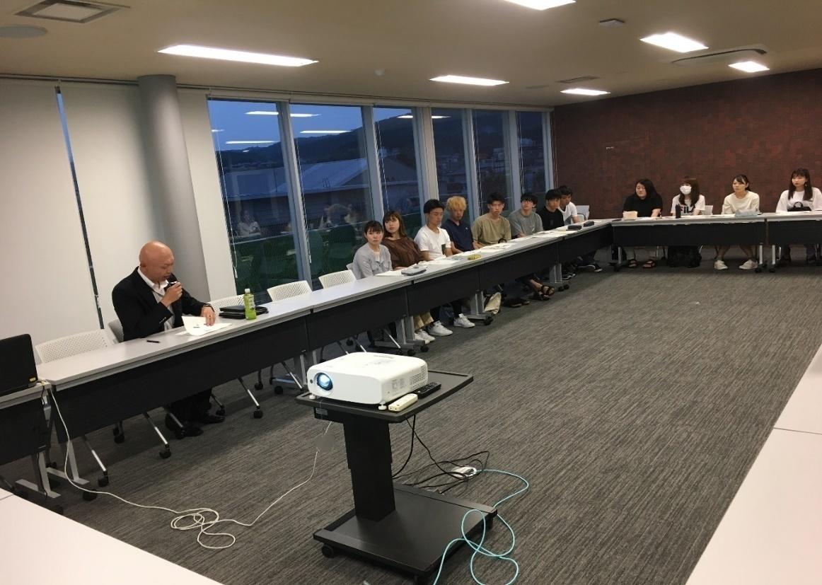 学生の報告に対してコメントされる岩崎部長と、それを聞くゼミ生(7月23日)